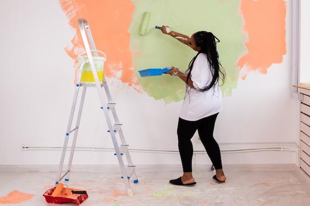 Feliz mulher afro-americana pintando a parede em seu novo apartamento. renovação, redecoração e reparo