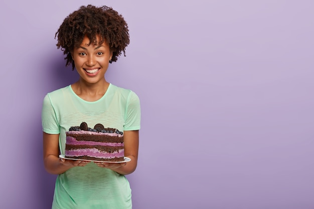 Feliz mulher afro-americana segurando um delicioso bolo de aniversário com mirtilo e presenteia os convidados com uma sobremesa doce saborosa Foto gratuita