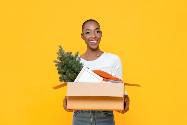 Feliz mulher afro-americana sorridente segurando caixa movendo coisas para a nova casa