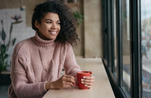 Feliz mulher afro-americana tomando café, olhando pela janela, fique em casa