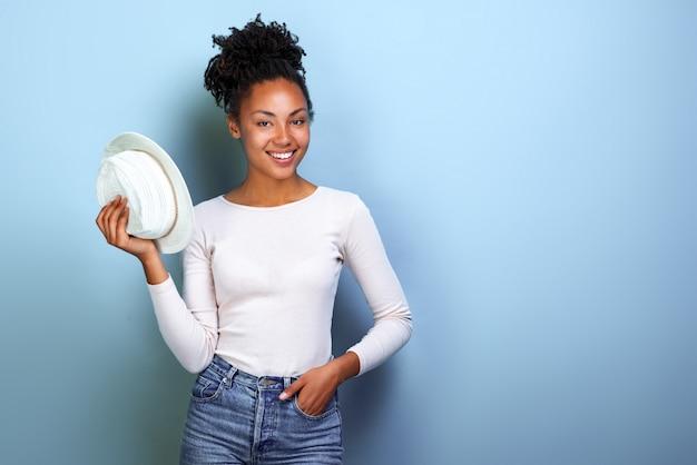 Feliz mulher afro-americana viajante segura o chapéu e olhando para a câmera