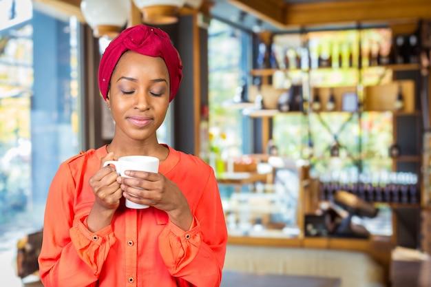 Feliz, mulher americana africana, bebendo, xícara chá, ou, assalte