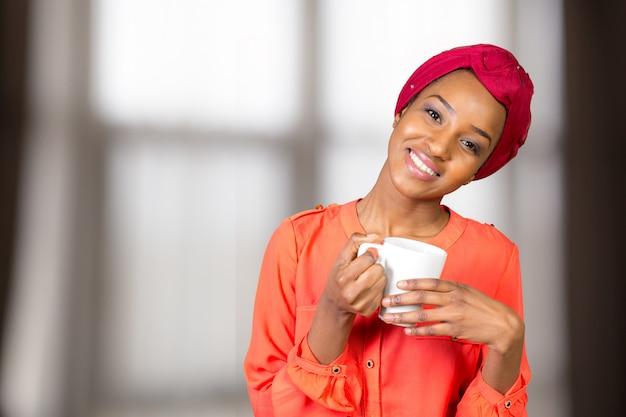 Feliz, mulher americana africana, chá bebendo, de, copo, ou, assalte