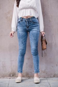 Feliz mulher ásia em jeans azul brilhante colheita magra, céu azul jeans