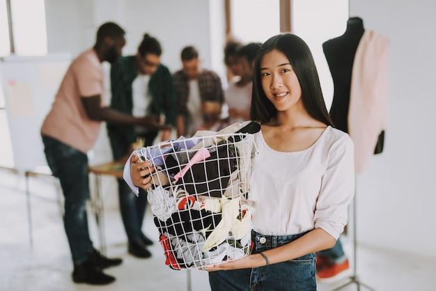 Feliz, mulher asian, é, cesta segurando, com, pano
