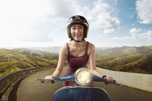 Feliz, mulher asian, montando, scooter azul, com, capacete