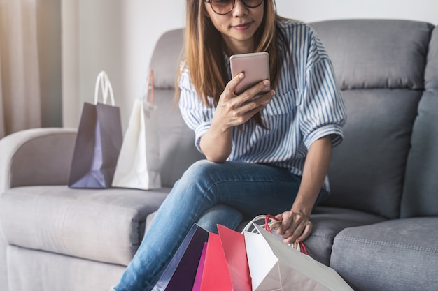 Feliz, mulher asian, segurando, cartão crédito, e, esperto, telefone