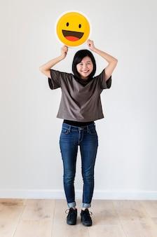 Feliz, mulher asian, segurando, um, smiley, emoticon, rosto
