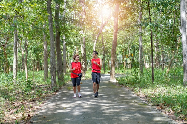 Feliz, mulher asian sênior, com, homem, ou, treinador pessoal, sacudindo, executando, parque