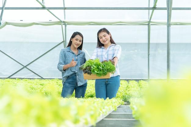 Feliz mulher asiática agricultor segurando uma cesta de legumes e tablet e sorrindo