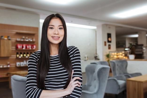 Feliz mulher asiática com os braços cruzados na cafeteria