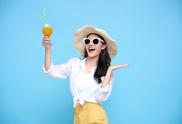 Feliz mulher asiática com roupas casuais de verão, usando chapéu de palha e óculos de sol segurando um copo de suco de frutas frescas isolado na parede azul brilhante
