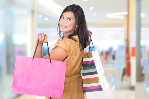 Feliz mulher asiática de meia-idade, segurando sacolas de compras