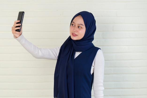 Feliz mulher asiática em hijab com telefone celular fazendo selfie.