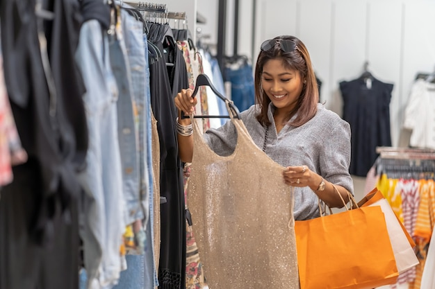Feliz mulher asiática escolhendo roupas com loja na loja com ação feliz no centro de departamento