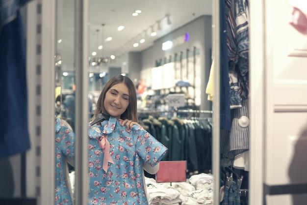 Feliz mulher asiática escolhendo roupas e olhando para o espelho no shopping ou loja de roupas.