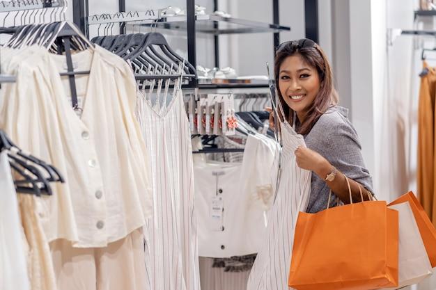 Feliz mulher asiática escolhendo roupas na loja loja com ação feliz no centro de departamento