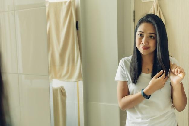 Feliz mulher asiática está penteando o cabelo no espelho do banheiro.