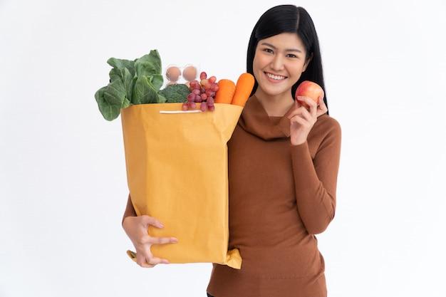 Feliz mulher asiática está sorrindo espera apple e carrega um saco de papel comercial