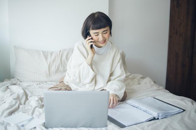 Feliz mulher asiática está usando o smartphone e trabalhando em sua cama.