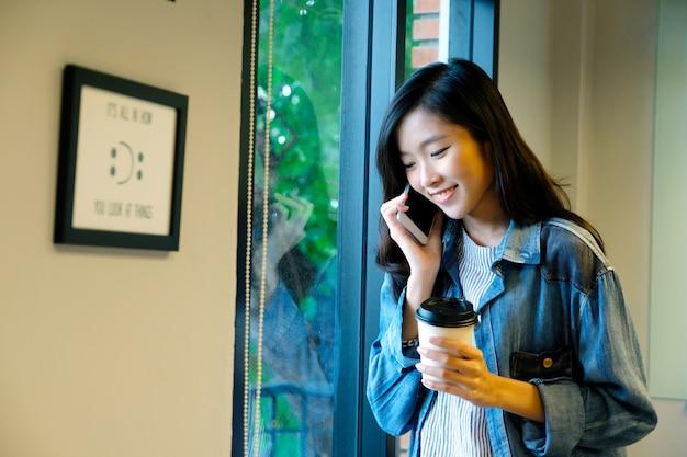 Feliz mulher asiática falando ao telefone enquanto segura a xícara de café