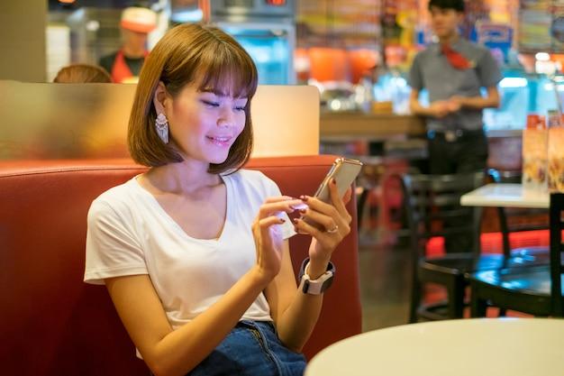 Feliz, mulher asiática, jogo, smartphone, em, restaurante