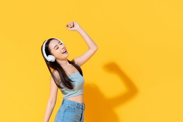 Feliz mulher asiática jovem no desgaste do verão ouvindo música de fones de ouvido e dançando isolado