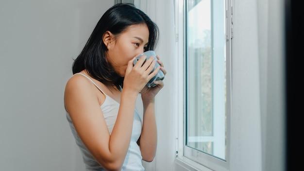 Feliz mulher asiática linda sorrindo e bebendo uma xícara de café ou chá perto da janela no quarto. jovem latina abrir cortinas e relaxar de manhã. senhora de estilo de vida em casa.
