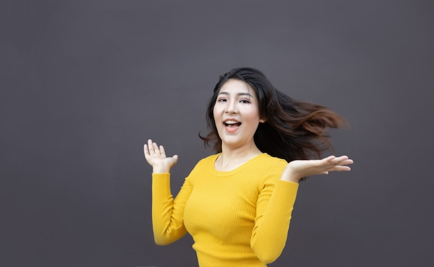 Feliz mulher asiática mão aberta e sorriso mostram cabelo comprido