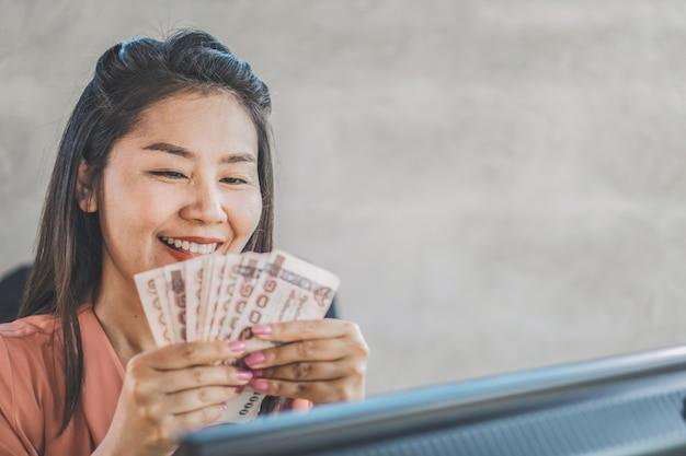 Feliz mulher asiática mão segurando as notas