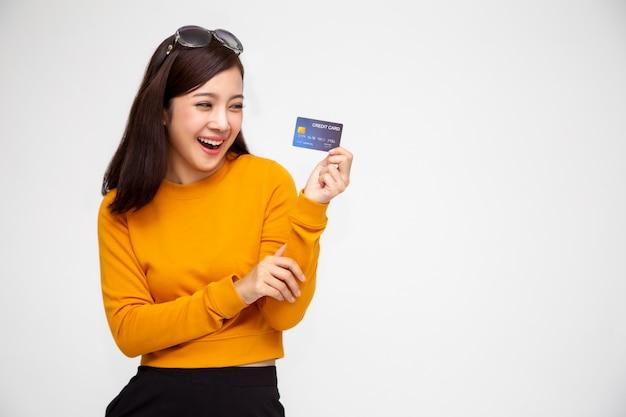 Feliz mulher asiática na camisa amarela, segurando o cartão de crédito