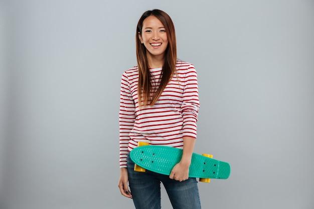 Feliz mulher asiática na camisola segurando o skate