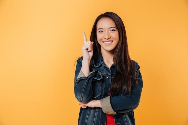 Feliz mulher asiática na jaqueta jeans apontando para cima