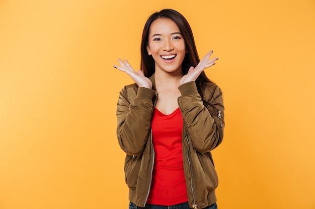 Feliz mulher asiática no casaco, segurando as mãos perto da cabeça