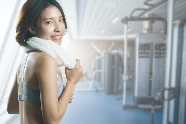 Feliz mulher asiática no centro de ginástica