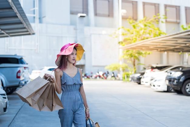 Feliz mulher asiática no vestido casual moda com sacos de compras e andar no estacionamento.