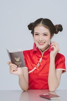 Feliz mulher asiática no vestido chinês tradicional segurando o passaporte