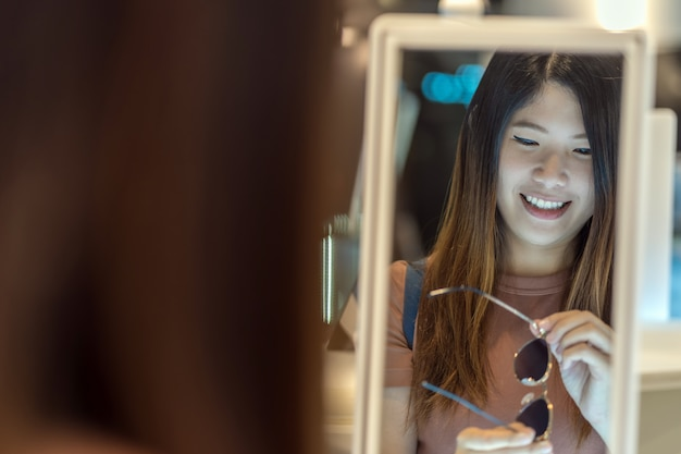 Feliz mulher asiática olhando e escolhendo óculos na loja de loja de departamento, compras e moda