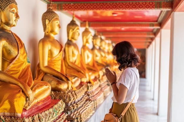 Feliz mulher asiática orando com buda