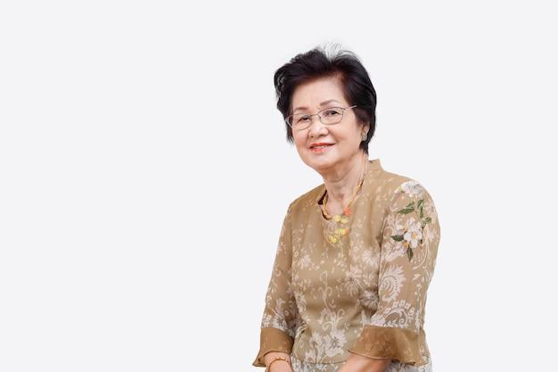 Feliz mulher asiática relaxando em casa, isolado no branco