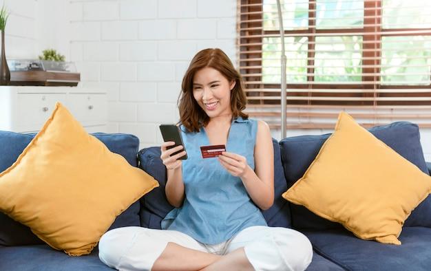 Feliz mulher asiática relaxando no confortável sofá usando smartphone e cartão de crédito, compras online em casa na sala de estar.