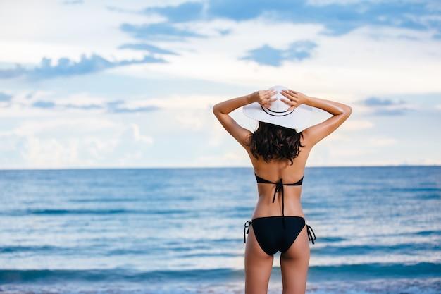 Feliz mulher asiática relaxar na praia. conceito das férias de verão, por do sol, chave da altura