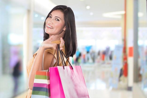 Feliz mulher asiática segurando sacolas de compras
