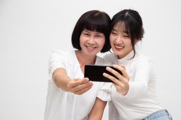 Feliz mulher asiática sênior e filha tomando selfie juntos isolado