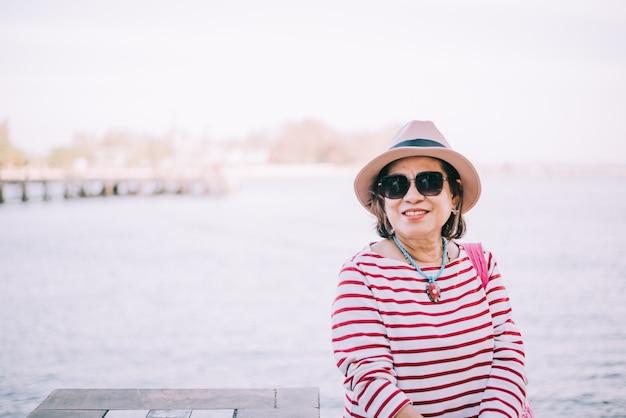 Feliz mulher asiática sênior sentado do lado de fora