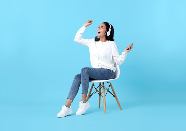 Feliz mulher asiática sentada na cadeira usando fone de ouvido sem fio, ouvindo música de smartphone em azul.