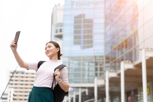 Feliz mulher asiática tomando uma selfie na cidade