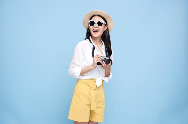 Feliz mulher asiática vestida com roupas de verão, segurando uma câmera fotográfica e olhando para longe isolada sobre fundo azul.