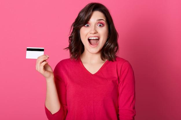Feliz mulher atônita com cartão de crédito na mão, olhando diretamente para a câmera com a boca amplamente aberta e grandes olhos, morena feminina ganhar grande soma de dinheiro.