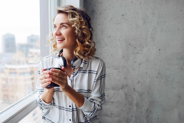 Feliz mulher atraente sentada no parapeito da janela, desfrutando de um chá quente num dia ensolarado de inverno.
